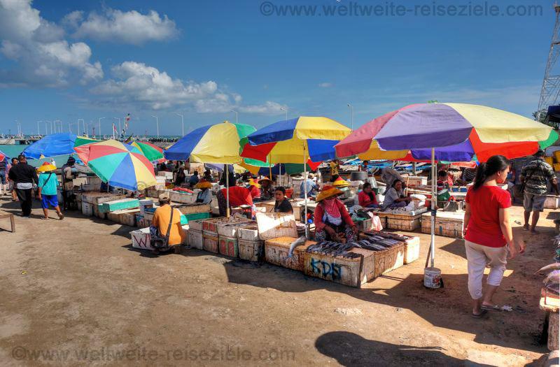 Bunte Sonnenschirme mit Fischverkäufern am Fischmarkt von Kendogan, Bali