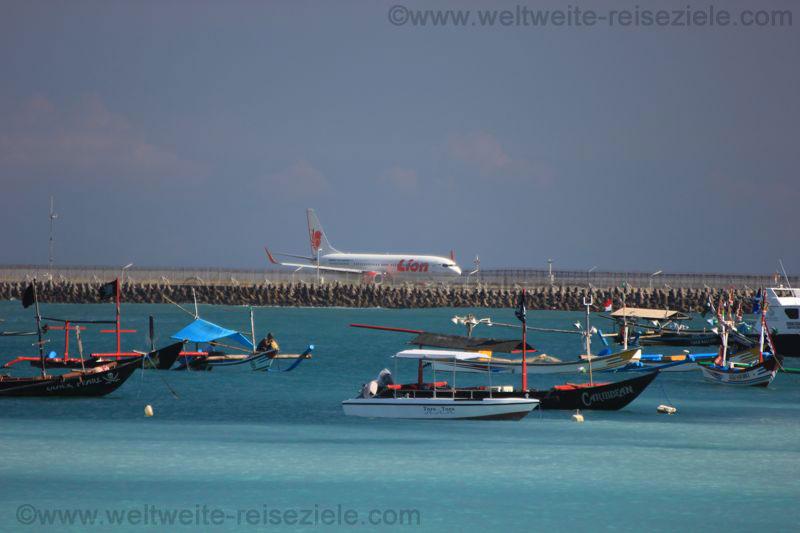 Fischerboote in der Bucht südlich vom Flughafen von Bali und Flugzeug startbereit auf der Startbahn