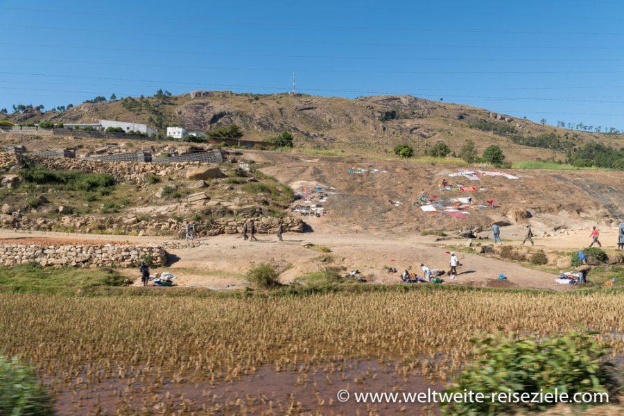 Reisfeld und bunte Wäsche zum Trocknen auf einem Felshügel, Madagaskar
