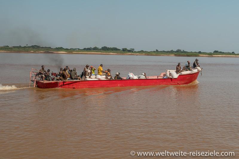 Rotes Schiff transportiert Einheimische und Erdnusssäcke über den Fluss Tsiribihina