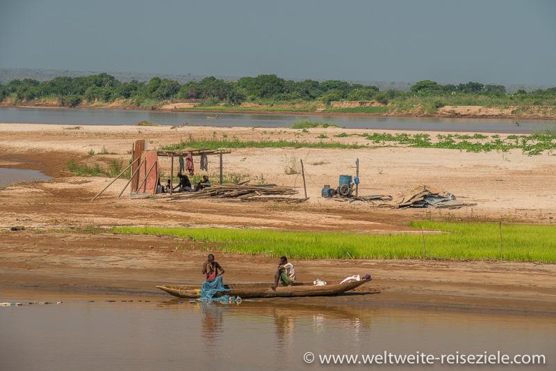 Einheimische Fischer mit Einbaum vor einer Sandbank mit grünem Reisfeld am Fluss Tsiribihina