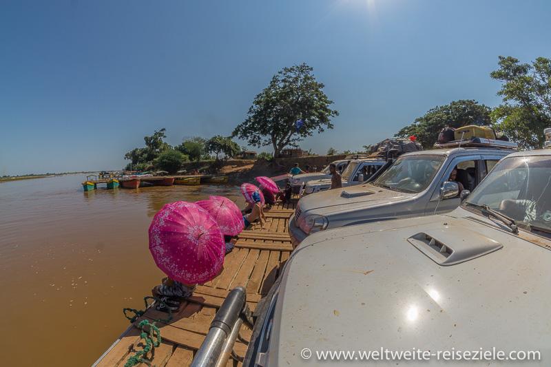 Autofähre mit Geländewagen und Touristen mit rosa bunten Sonnenschirmen am Fluss Tsiribihina