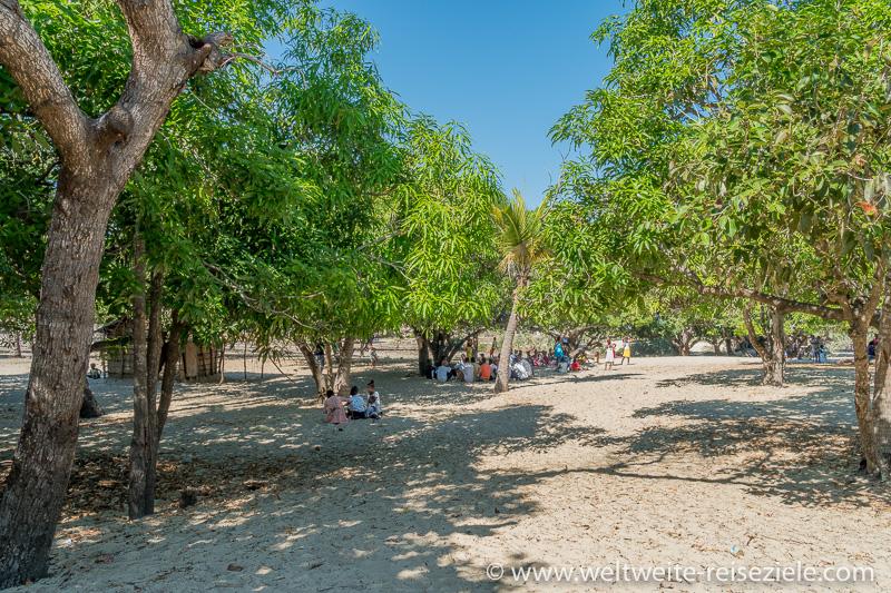 Dorfplatz im Sand mit Einheimischen unter den Bäumen, Betania, Morondava