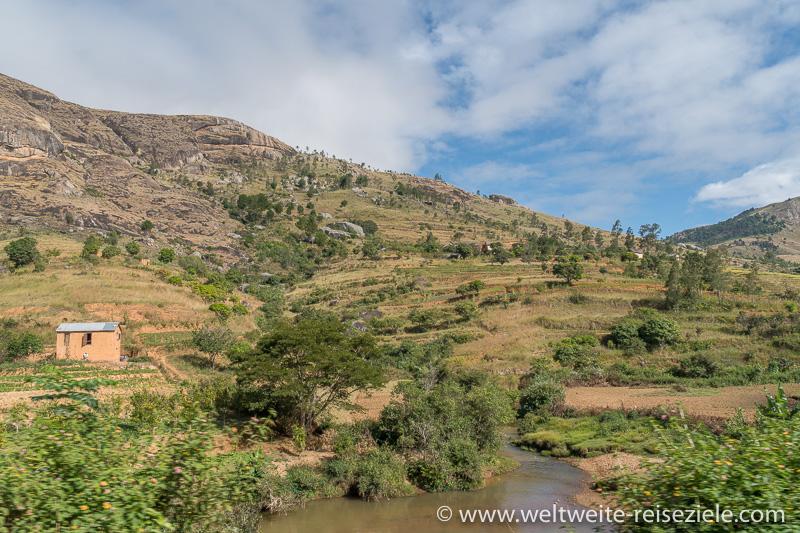 Fluss mit typischem Haus und Felshügel im Zentrum von Madagaskar