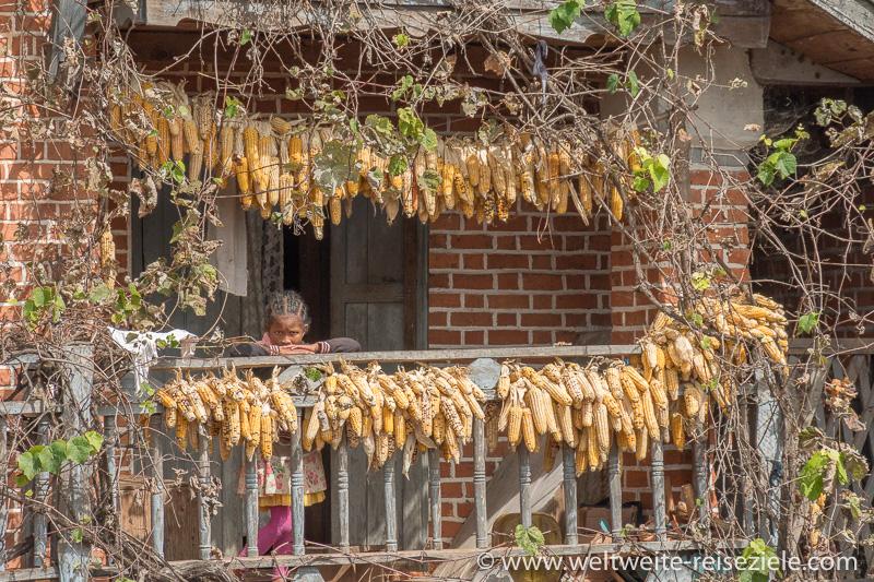 Holzbalkon mit einheimischen Kind und trockenem orangen Mais, Ivato, Madagaskar