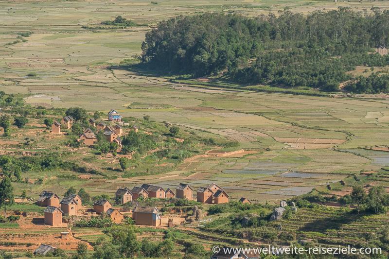 Reisfelder und kleines Dorf mit typischen braunen Lehmziegel Häusern, Madagaskar Zentrum