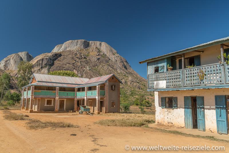 Zwei typische Häuser von Madagaskar mit Holzhalonen vor den rundlichen Felsbergen im Reservat von Anja