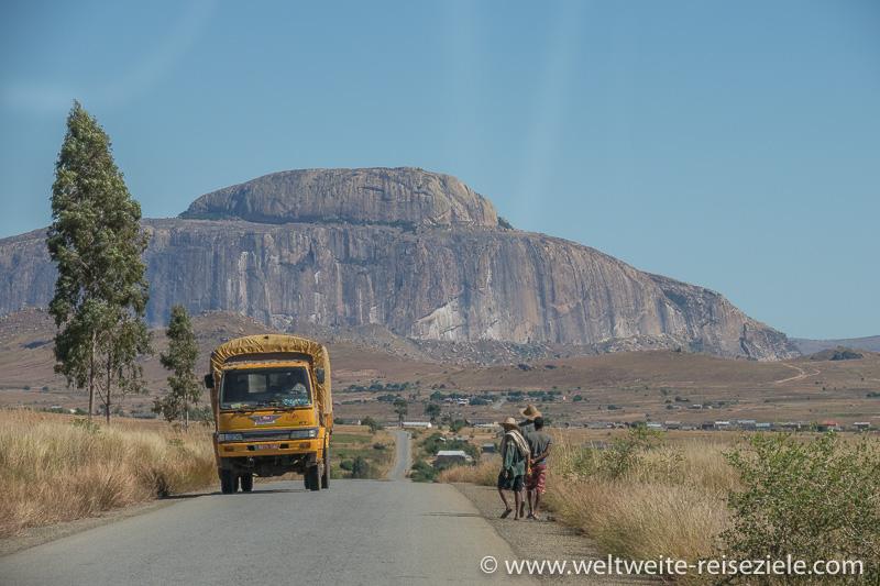 Grosser runder Felsen, gelber Lastwagen und gerade Strasse vor Ihosy, Madagaskar
