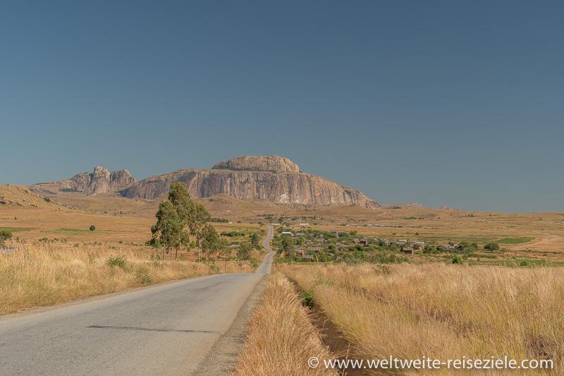 Lange, gerade Strasse führt durch Grasland auf einen grossen runden Felsberg, Ihosy, Madagaskar