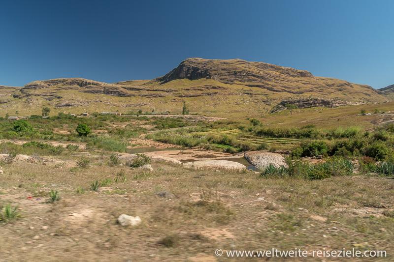 Hochland Graslandschaft mit kleinen Reisfelder und Felsbergen im Hintergrund, Ambalavao nach Ihosy, Madagaskar