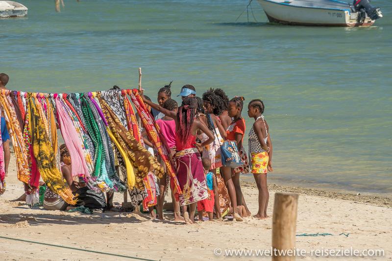 Einheimische beim Kauf von bunten Tüchern am Strand von Mangily