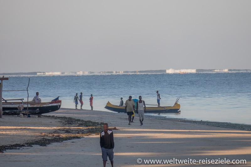 Einheimische und Fischerboote, im Hintergrund hohe Wellen und Brandung am Riff vor Mangily