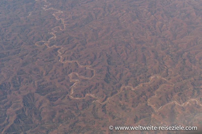 Fluss schlängelt sich durch die trockene Hochebene von Madagaskar, vom Flugzeug aus fotografiert