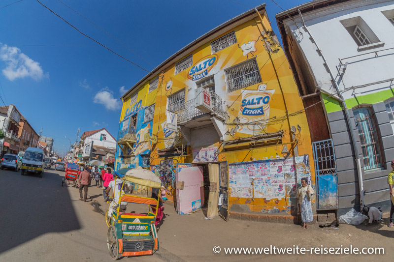 Gelbes Haus mit Werbefläche und Fahrrad Rikscha davor, Madagaskar