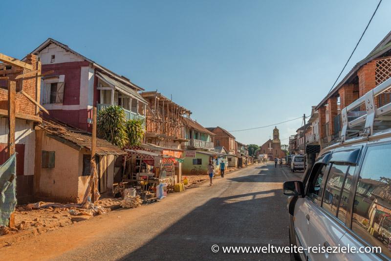 Hauptstrasse von Mandoto mit typischen Häusern und der Kirche mit umgedrehtem Kreuz im Hintergrund