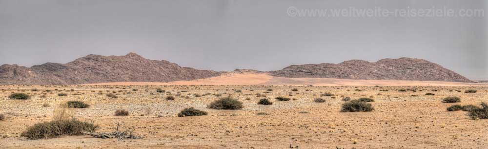 Dunkle Felsen und Sanddünen in der Namib, Namibia