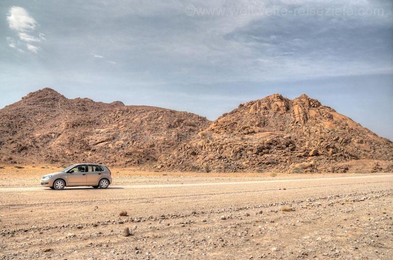 unser Mietwagen vor uralten Felsen in der Namibwüste