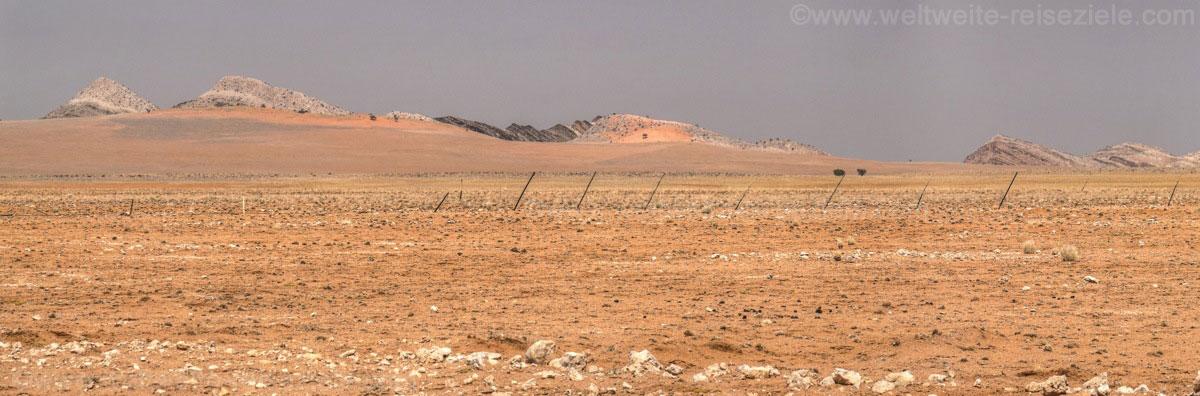 Dünen mit schwarzen Felsen an der Strasse von Solitaire zum Gaub Canyon