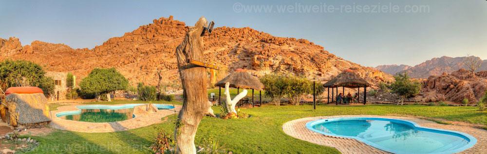 Zwei Pools der White Lady Lodge im Garten, dahinter der Felsberg