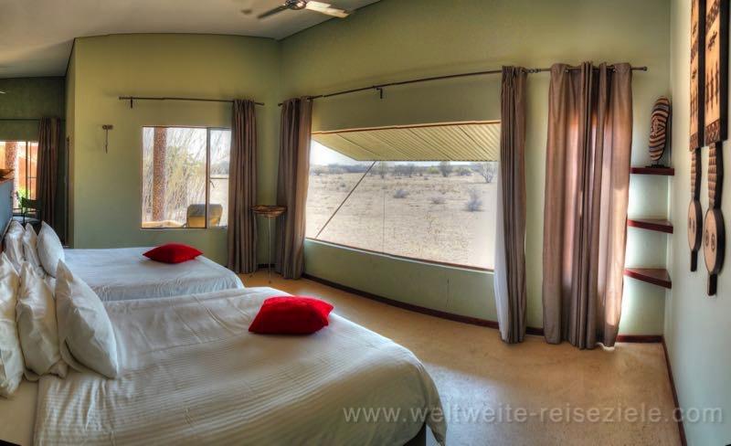 Grosses Bett mit Aussicht durch das Panoramafenster auf die davor liegende Ebene, Standart Chalet, Okonjima Lodge