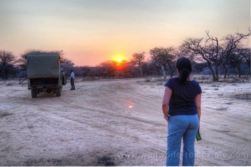 Sundowner bei Sonnenuntergang im Busch der Okonjima Lodge, Namibia